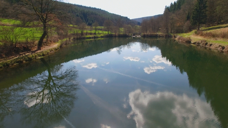 The water surface of the Eutersee is reflecting the clouds. The Eutersee is a little lake in South Hessia, Germany. Stock Photo