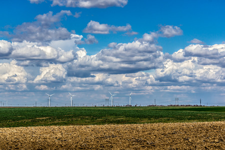 eolian: Fluffy clouds over plowed field with eolian turbines