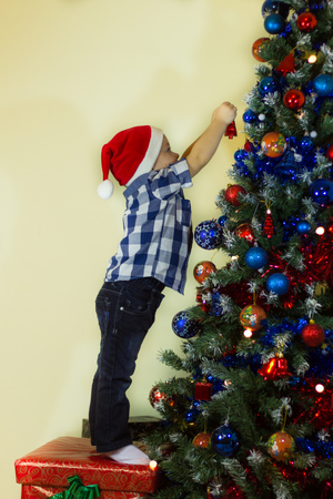 box tree: Little boy decorating the Christmas tree trying to reach as high as possible