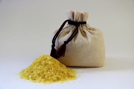 Sea yellow salt in a bag. Isolated. A bag of sea salt produced on a farm