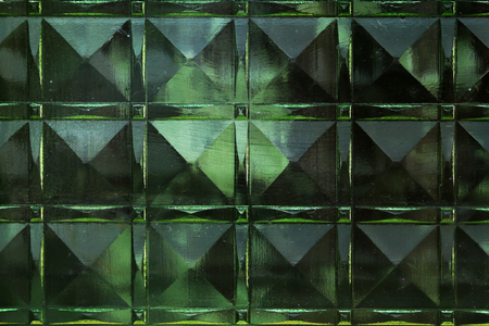 Green texture of thick glass in the form of squares, background.
