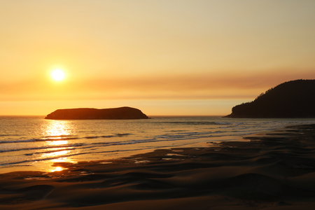 Beautiful sandy beach on the Pacific Ocean during a bright sunset. Foto de archivo