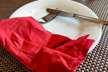White plate with fork and knife and napkin on the table after eating