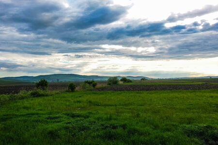 Dramatic sky and green meadows, in the distance one can see mountains, nature background