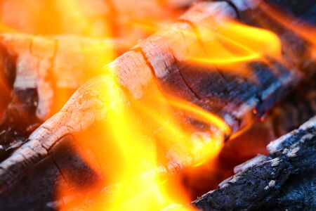Beautiful color of burning red coals and black charred wood. Orange hot coals in the Russian stove. Red burning coals as a texture for design 写真素材