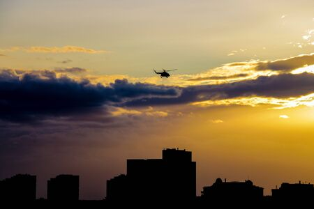 A helicopter flies over the city in the evening during sunset Stockfoto