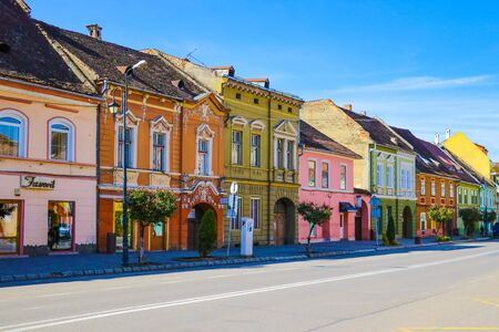 Sighisoara, Romania, May 11, 2019: Stone paved old street and cafe bar with colorful retro buildings in city center, Sighisoara fortress, Transylvania, Romania, Europe