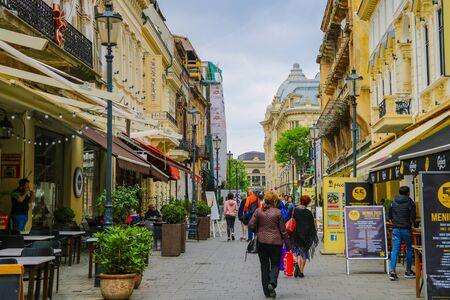 Bucharest, Romania, May 17, 2019: Tourists and locals walk along the old street of Bucharest, many cafes and souvenir shops 報道画像