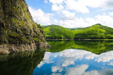 Nice view of the mountains and green hills. Reflection of hills in a lake