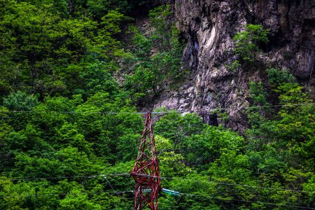 Electric pole power line structure with mountains in background 写真素材