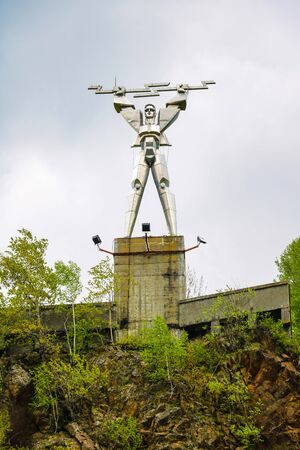 Romania - May 12, 2019: Energia statue by Constantin Popovici, representing Prometheus with lightning in his hands, symbolizing electricity, at the edge of Vidraru lake