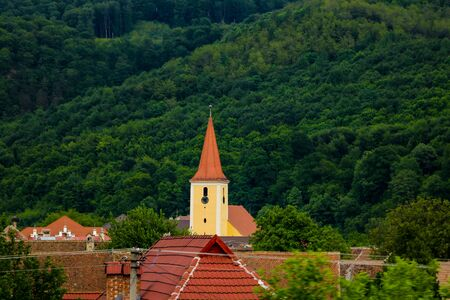 Sibiu, Romania, May 15, 2019: Roofs of old houses on a background of green mountains