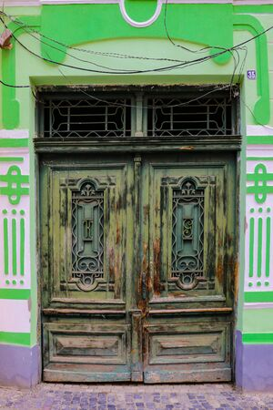 Sibiu, Romania, May 15, 2019: Traditional, colorful, decaying wooden courtyard doors of old townhouses in the center 報道画像