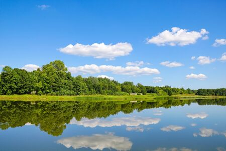 Reflection of white clouds and forest in a river or lake on a sunny day, nature