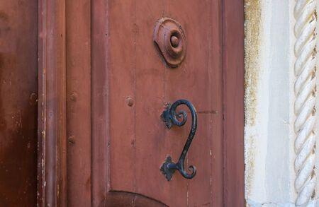 Iron black doorknob against the background of red doors