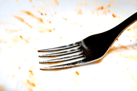 View of a dirty white plate with a fork after eating