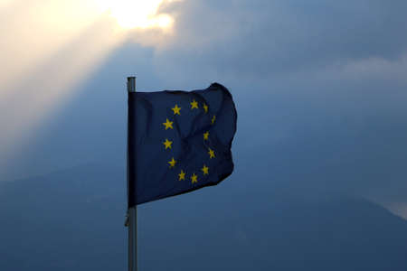 The flag of the european union flies in the wind against a dark sky from which the sun's rays break through