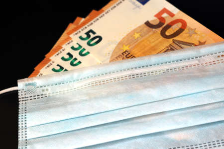 The protective mask lies on the euro banknotes. Coronavirus concept. The collapse of the global economy from COVID - 19