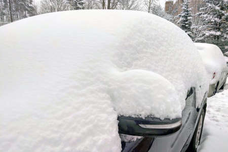 The car is covered with snow. Snowfalls in Europe and America