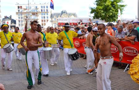 LE MANS, FRANCE - JUNE 13, 2014: Brazilian man dancing at a parade of pilots racing.