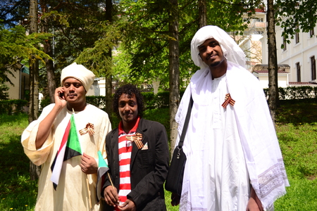 soviet flag: PYATIGORSK, RUSSIA - MAY 09, 2011: African men are dressed in national costumes and in solidarity pinned St. George Ribbon.
