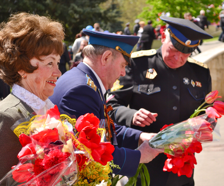 grizzled: PYATIGORSK, RUSSIA - MAY 09, 2011: Woman and two military men with tulips on Victory Day. 9 may Editorial