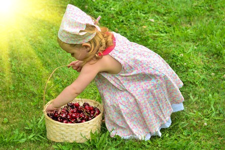 Girl in a dress with a basket of red cherries Stock Photo