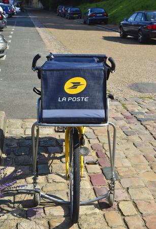 le cap: LE MANS, FRANCIA - 31 DE AGOSTO DE 2017: Bicicleta amarilla de una oficina de correos La Poste de la ciudad francesa parqueó en la calle de Le mans. el cartero fue a entregar el correo