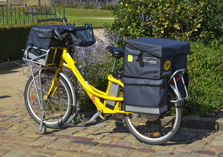 le cap: LE MANS, FRANCE - AUGUST 31, 2017: Yellow bicycle of a post office La Poste of French city parked on the street of Le mans. postman went to deliver the mail Editorial