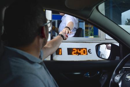 Een man betaalt geld aan een kassier voor een tolweg Tolpoort ingang snelweg