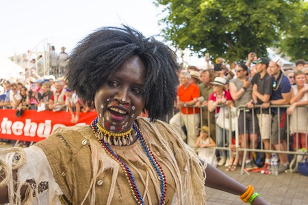 LE MANS, FRANCE - JUNE 16, 2017: African woman in national clothes dancing at the opening parade of 24 hours of Le mans ,France. African entertainments. Editorial
