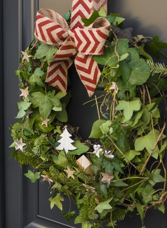 Front door with a Christmas wreath of ivy and bows. Stock Photo