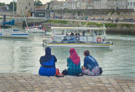 LA ROCHELLE, FRANCE - AUGUST 12, 2015: Muslim woman wearing hijab looking on the ocean and yachts at La Rochelle, France.