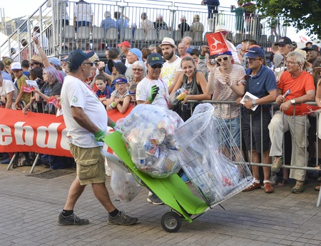 LE MANS, FRANCE - JUNE 16, 2017: Worker Man Collecting Garbage with cans and plastic on the street during the parade of pilots Editorial