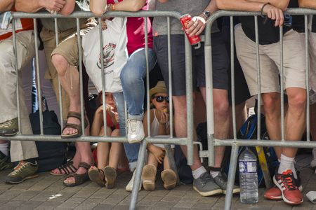 LE MANS, FRANCE - JUNE 16, 2017: A crowd of people and children behind the barrier at a Parade of pilots racing at Le mans, France