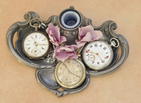 Old vintage pocket antique clock on a metal plate Stock Photo