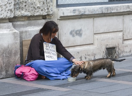 TOULOUSE, FRANCE - JULY 23, 2016: A hungry woman begs alms on the street of Toulouse with words Im hungry. Help me. Thank you.