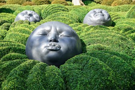 ETRETAT, FRANCE - SEPTEMBER 02, 2018: Giant rubber heads sleeping on green pillows. Boxwood garden in the famous garden of Etretat, Normandy, France