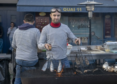 DIEPPE, FRANCE - NOVEMBER 17, 2018: Man cooks herring on the grill. Fair Herring and scallop shell on the market