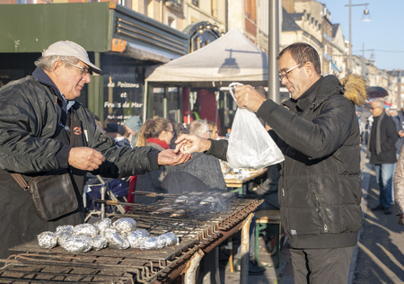 DIEPPE, FRANCE - NOVEMBER 17, 2018: The buyer buys herring on the grill and potatoes in foil. Fair Herring and scallop shell.