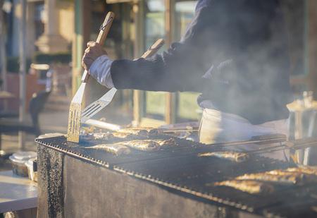 Man cooks herring on a grill on the market 版權商用圖片