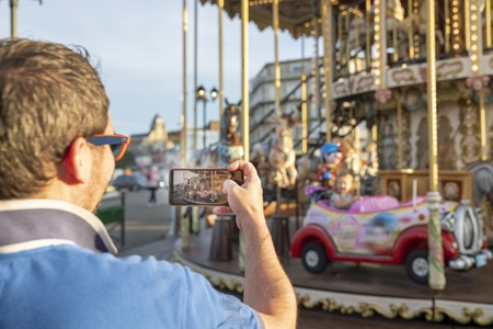 Father takes photos or videos of his daughter on the carousel on the phone