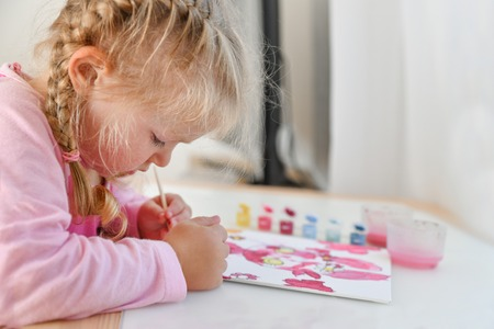 The girl paints the picture with her left hand in color paints