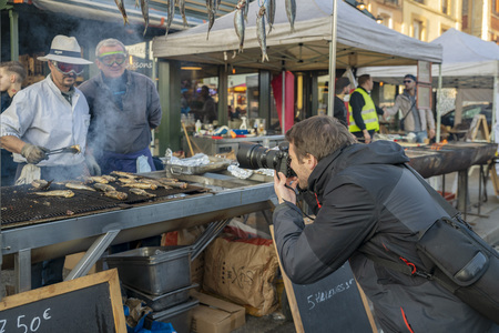DIEPPE, FRANCE - NOVEMBER 17, 2018: A photographer photographs herring sellers. Fair Herring and scallop shell on the local market