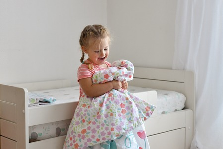 A girl makes a bed in the childrens room
