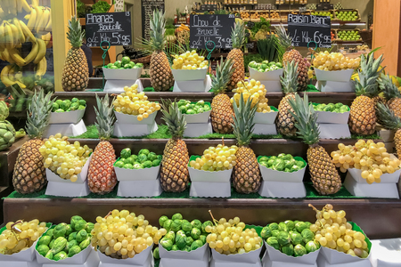 Fresh grapes pineapples and Brussels sprouts on the grocery store in the supermarket in France