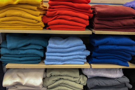 Rows of folded colorful clothes in a shop 版權商用圖片