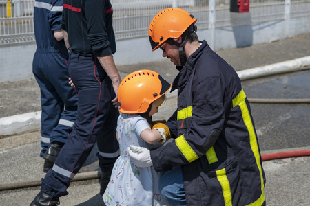 Fire uniformed father teaches his daughter Firefighter training