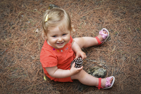 Little girl holding a cone in the woods