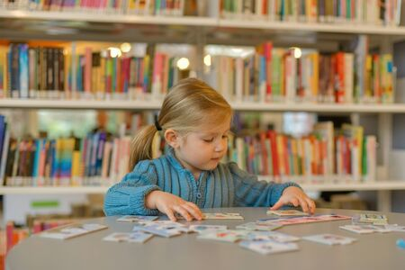 Little girl playing puzzle in a library 版權商用圖片